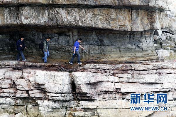 """-->  一位游客在海蚀作用形成的石楼内游览 神奇""""栈道""""引游客(图) 位于渤海湾的山东长岛县大黑山岛是一座火山岛。亿万年的风化和海蚀作用在岛东端的石英岩上形成了一条数公里长的栈道,长岛渔家乐随着海平面下降,栈道露出水面,成为一条天然的道路。据地质部门勘察,海蚀栈道包含了大量古生物、海洋运动信息,具有较高的地质学研究价值。目前大黑山岛已成为长岛国家地质公园的主体部分,长岛旅游攻略每年吸引大量专家学者和游客前来参观。  位于崖壁中的栈道(6月19日摄)。  几位游客行走在海蚀栈道"""
